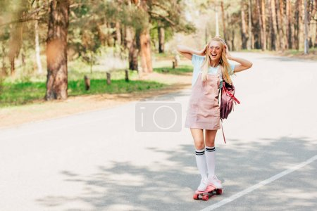Photo for Full length view of excited blonde girl skateboarding and listening music in headphones - Royalty Free Image