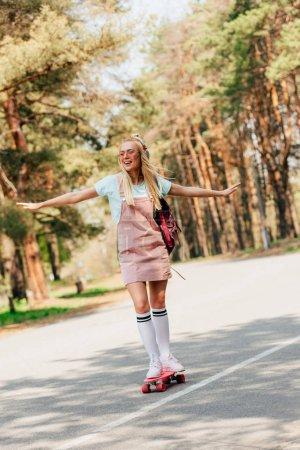 Photo pour Vue pleine longueur de la planche à roulettes blonde excitée de fille et écoutant la musique dans des écouteurs - image libre de droit