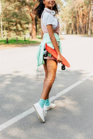 Photo pour Cropped view of african american girl standing on road and holding penny board - image libre de droit