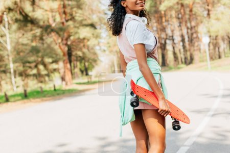 Photo pour Vue recadrée de fille américaine africaine restant sur la route et retenant le panneau de penny - image libre de droit