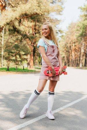 Photo pour Vue pleine longueur de la fille blonde de sourire restant sur la route et retenant le panneau de penny - image libre de droit
