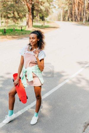 Photo pour Vue pleine longueur de la fille américaine africaine dans le casque restant sur la route et retenant le panneau de penny - image libre de droit