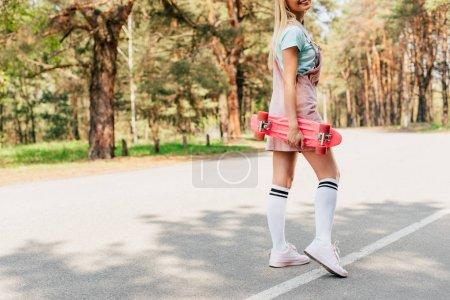 Photo pour Vue recadrée de fille blonde de sourire restant sur la route et retenant le panneau de penny - image libre de droit