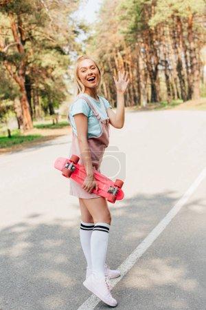 Photo pour Vue pleine longueur de la fille blonde de sourire restant sur la route avec le conseil de penny et la main ondulante - image libre de droit