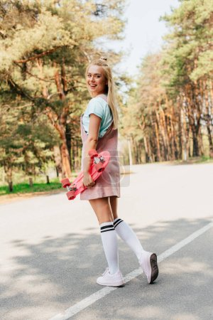 Photo for Full length view of smiling blonde girl standing on road and holding penny board - Royalty Free Image