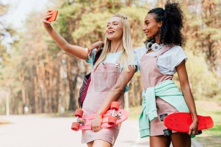 Photo for Two smiling multiethnic friends holding penny boards and taking selfie on road - Royalty Free Image
