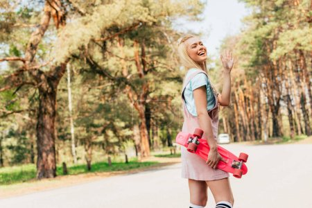Photo pour Excited blonde girl holding penny board and waving hand on road - image libre de droit