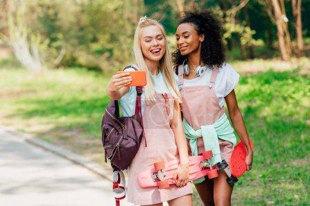Photo pour Deux amis multiculturels souriants avec des planches de penny prenant le selfie sur la route - image libre de droit