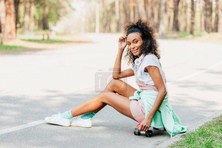 Photo pour Fille américaine africaine de sourire avec des écouteurs s'asseyant sur le panneau de penny sur la route - image libre de droit