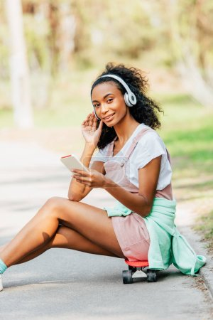 smiling african american girl listening music in headphones and using smartphone while sitting on penny board