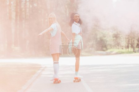 Photo for Full length view of two girls skateboarding on penny boards in smoke on road - Royalty Free Image