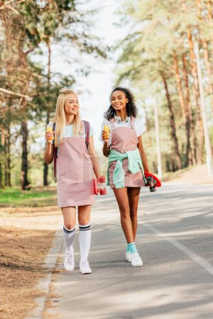 Foto de Vista de longitud completa de dos amigos multiculturales con tablas de centavos que sostienen botellas de jugo de naranja mientras camina por la carretera - Imagen libre de derechos