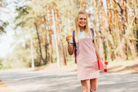 Photo pour Fille blonde de sourire avec la bouteille de fixation de planche à roulettes du jus d'orange sur la route - image libre de droit