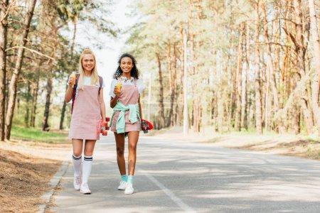 Photo pour Vue pleine longueur de deux amis multiculturels avec des planches de penny retenant des bouteilles de jus d'orange tout en marchant sur la route - image libre de droit
