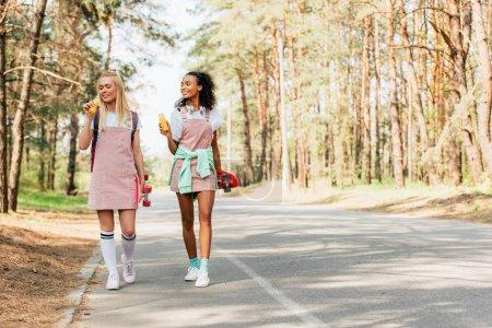 Photo pour Vue pleine longueur de deux amis multiethniques avec des planches de penny retenant des bouteilles de jus d'orange sur la route - image libre de droit