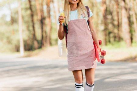 Photo pour Vue recadrée de fille blonde de sourire avec la bouteille de fixation de penny de panneau de jus d'orange sur la route - image libre de droit