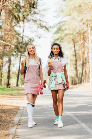 Photo for Full length view of two multiethnic friends with penny boards holding bottles of orange juice on road - Royalty Free Image