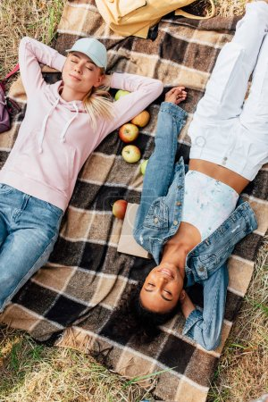 Photo pour Top view of two smiling multiethnic girls lying on plaid blanket with apples - image libre de droit