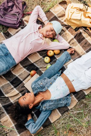 top view of two smiling multiethnic girls lying on plaid blanket with apples