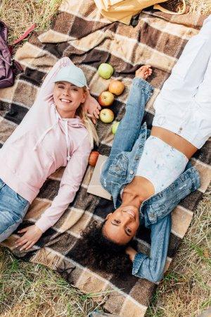 Foto de Vista superior de dos chicas multiétnicas sonrientes acostado en manta a cuadros con manzanas - Imagen libre de derechos