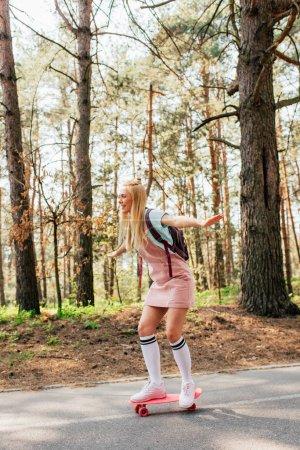 Photo for Full length view of blonde girl in knee socks skateboarding on road - Royalty Free Image