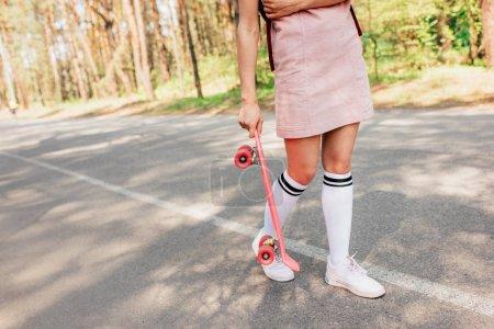 Photo pour Vue recadrée de fille dans des chaussettes de genou retenant le panneau de penny sur la route - image libre de droit