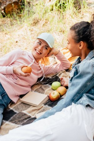 Photo for Two smiling multiethnic friends looking at each other on plaid blanket with apples - Royalty Free Image