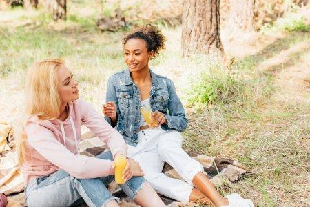 Foto de Dos chicas multiétnicas sentadas en una manta a cuadros y sosteniendo botellas de jugo de naranja - Imagen libre de derechos