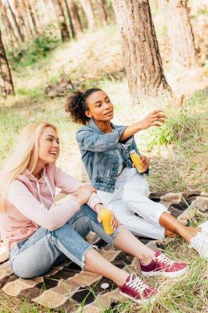 Photo for Two multiethnic girls sitting on plaid blanket and holding bottles of orange juice - Royalty Free Image