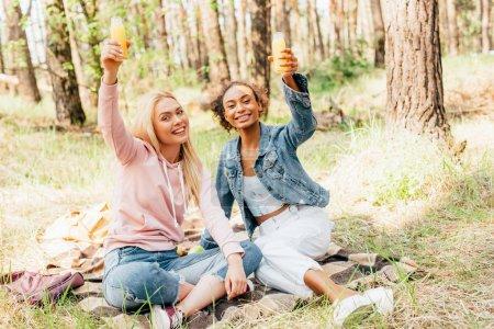 Photo for Two multiethnic girls sitting on plaid blanket and raising bottles of orange juice - Royalty Free Image