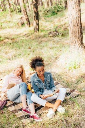 Foto de Two multiethnic friends sitting on plaid blanket and reading books - Imagen libre de derechos