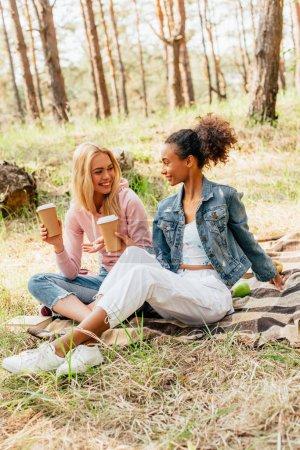 zwei multiethnische Freunde sitzen auf karierter Decke und halten Pappbecher mit Kaffee in der Hand