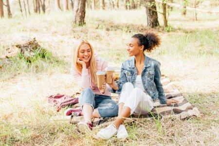 Photo pour Deux amis multiethniques assis sur une couverture à carreaux et tenant des tasses de café en papier - image libre de droit