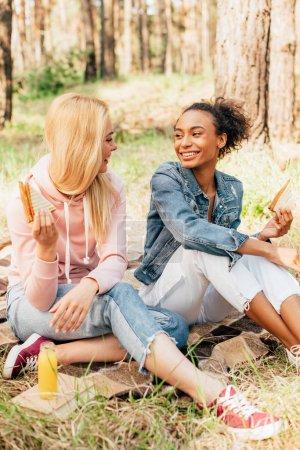 Photo pour Deux amis multiethniques souriants s'asseyant sur la couverture avec des sandwichs et regardant l'un l'autre - image libre de droit