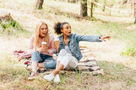 Photo pour Deux amis multiethniques étonnés assis sur le plaid avec des tasses de papier de café et regardant loin - image libre de droit