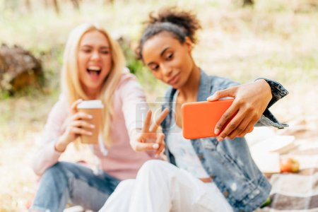 Photo pour Foyer sélectif de deux amis souriants multiculturels avec tasse en papier de café prendre selfie et montrant signe de paix - image libre de droit