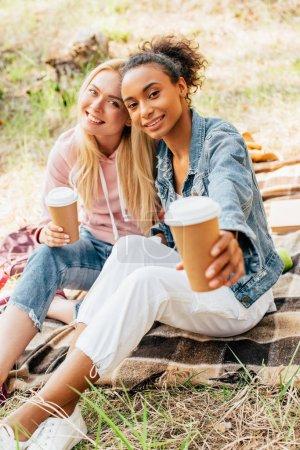 Foto de Dos amigos multiétnicos sentados en una manta a cuadros y sosteniendo tazas de papel de café - Imagen libre de derechos