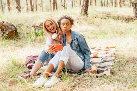 Photo for Two joyful multicultural friends with paper cups of coffee taking selfie in forest - Royalty Free Image