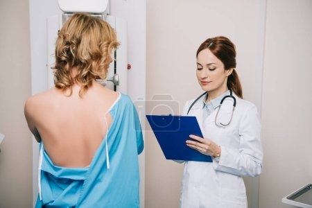 Photo for Beautiful young doctor looking at clipboard while standing near patient during mammography test on x-ray machine - Royalty Free Image