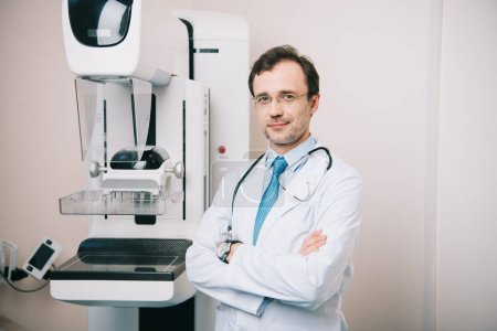 Photo pour Médecin souriant debout avec les bras croisés près de la machine à rayons X et regardant la caméra - image libre de droit
