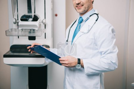 Photo for Partial view of doctor holding clipboard while standing at x-ray machine - Royalty Free Image