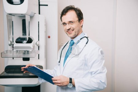 Photo for Smiling radiologist holding clipboard while standing at x-ray machine and looking at camera - Royalty Free Image