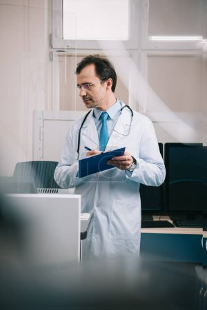 Photo for Selective focus of handsome doctor in white coat writing on clipboard - Royalty Free Image