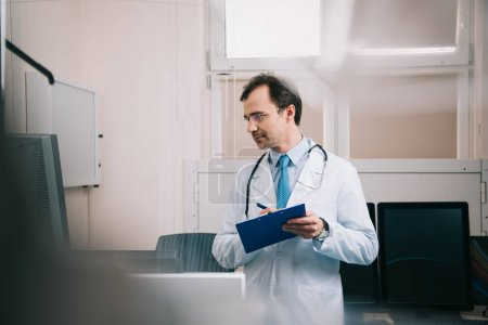 Photo pour Foyer sélectif du docteur souriant écrivant sur le presse-papiers et regardant loin - image libre de droit