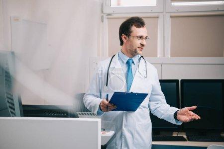 Photo pour Mise au point sélective de beau médecin gesticulant tout en tenant le presse-papiers - image libre de droit