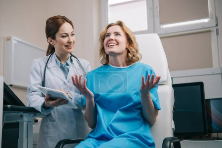 Photo pour Happy woman gesturing and looking up near smiling doctor holding digital tablet - image libre de droit
