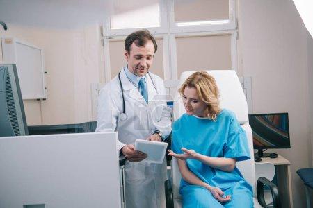Photo pour Foyer sélectif de beau médecin montrant tablette numérique à la femme souriante - image libre de droit