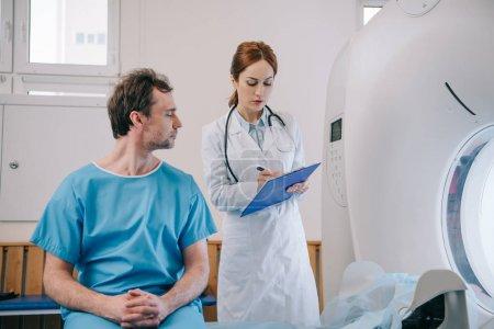 Mann sitzt auf Bett neben aufmerksamem Radiologen und schreibt auf Klemmbrett