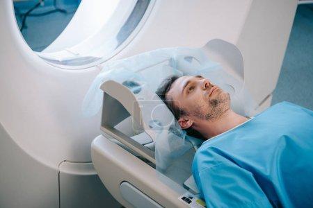 Photo pour Adulte bel homme couché sur lit ct scanner pendant le test de tomographie - image libre de droit