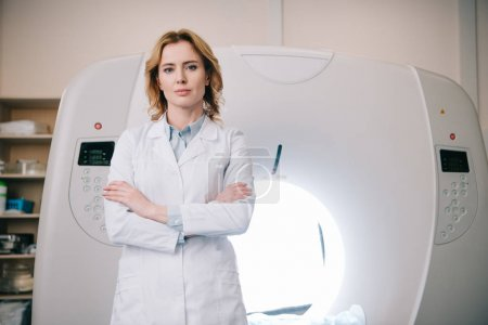 Photo for Attractive confident radiologist standing near mri machine with crossed arms and looking at camera - Royalty Free Image